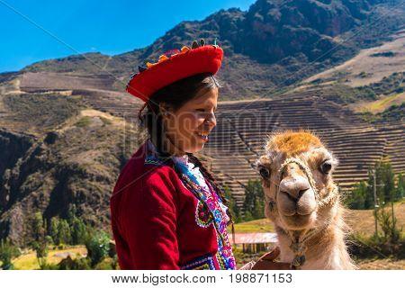 Native Peruvian girl with her lama animal in Sacred Valley, Cusco, Peru