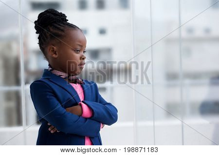 Contemplated businesswoman with arms crossed standing by glass window in office