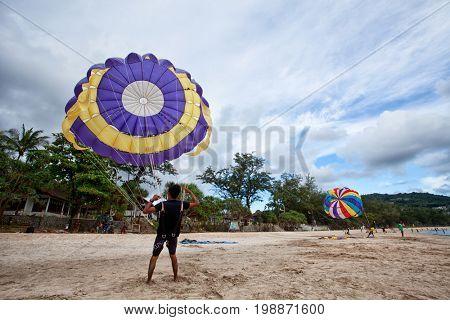 PHUKET – JULY 28, 2017, THAILAND : Parasailing at Patong Beach in Phuket. Thailand extreme sport