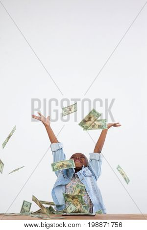 Cheerful businesswoman throwing paper currency in mid-air at office