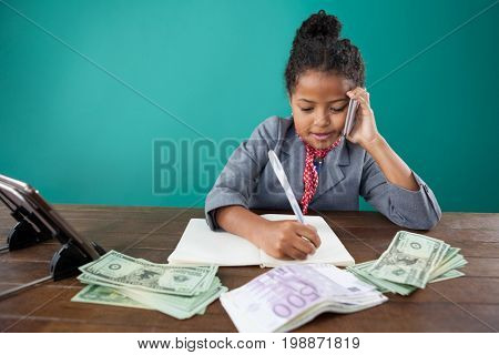 Businesswoman using phone while writing on book by paper currency at desk against blue background