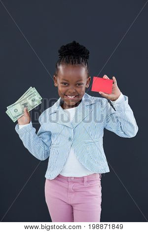 Portrait of businesswoman holding red card and paper currency while standing against gray wall