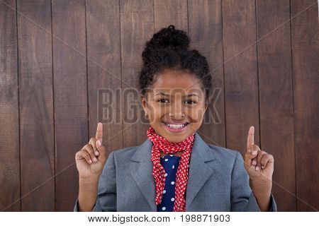 Portrait of smiling girl pretending as businesswoman pointing upwards while standing against white background
