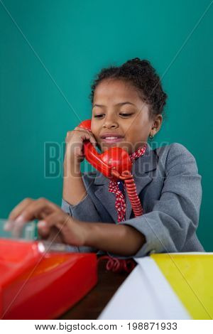 Close up of smiling businesswoman dialing numbers on land line phone while sitting at desk against blue background