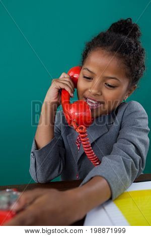 Happy businesswoman talking on land line phone at desk against blue background