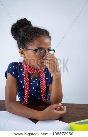 Thoughtful girl imitating as businesswoman sitting at desk against white background