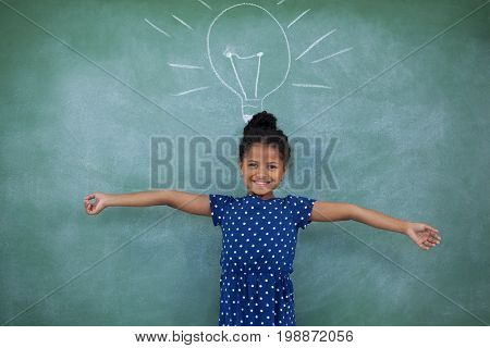 Portrait of girl with arms outstretched standing by bulb drawing on wall