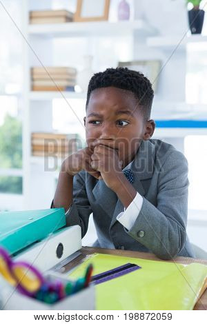 Thoughtful boy pretending as businessman sitting at desk in office