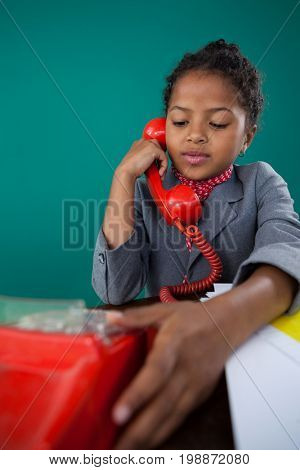 Girl pretending as businesswoman talking on land line phone while sitting at desk against blue background