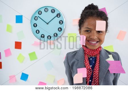 Happy businesswoman with adhesive notes stuck on suit and head standing against wall