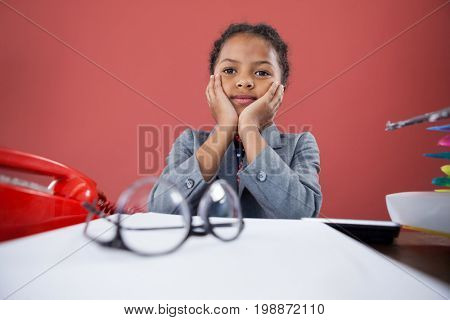 Girl imitating as businesswoman sitting with hand on chin at desk against orange background