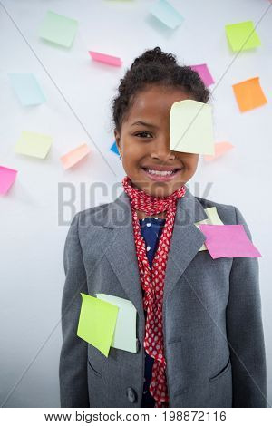 Happy businesswoman with sticky notes stuck on suit and head standing against wall