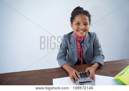 Portrait of happy girl pretending as businesswoman using calculator while working at desk