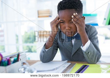 Boy as businessman with head in hand sitting at desk in office