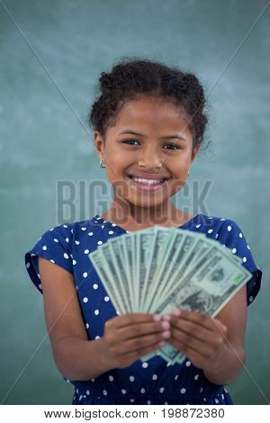 Close up portrait of smiling girl showing paper currency against wall