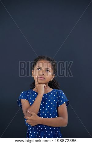 Contemplated girl with hand on chin standing against black backgroun