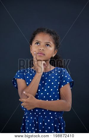 Girl with hand on chin standing against black background