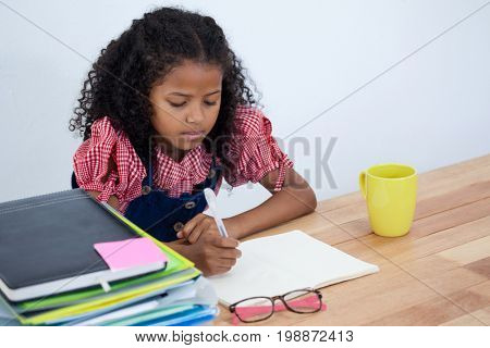 Girl imitating as businesswoman writing on book while sitting at table against white background