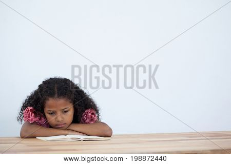 Businesswoman reading book while leaning on desk against white background