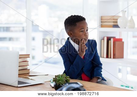 Thoughtful businessman with hand on chin looking away sitting at desk if office