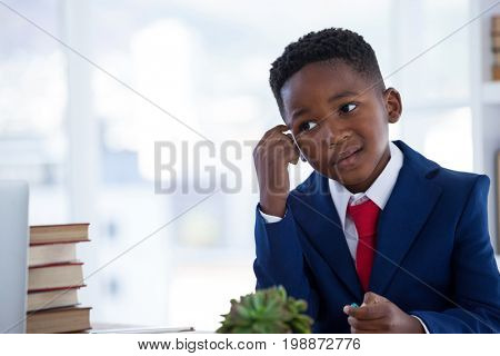 Close up of confused businessman with head in hand working at desk in office