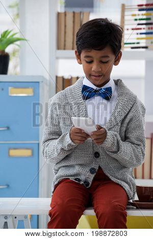 Boy pretending as businessman using mobile phone while sitting on desk in office
