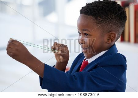 Side view of boy playing with rubber band in office