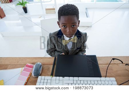 High angle portrait of boy imitating as businessman sitting at desk in office