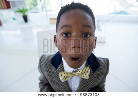 Close up portrait of boy imitating as businessman in office