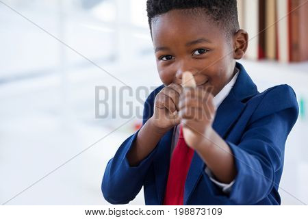Portrait of boy imitating as businessman playing with rubber band while standing in office