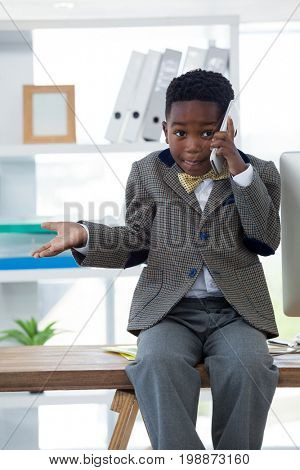 Boy imitating as businessman gesturing while talking on smartphone at desk in office