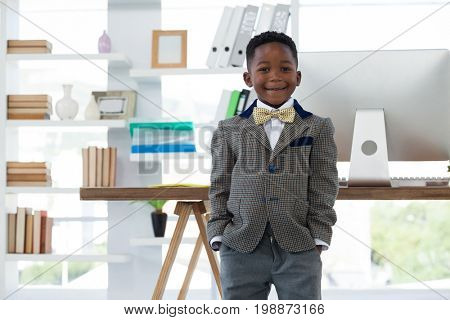 Portrait of boy imitating at businessman standing in office