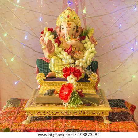A Ganesh Puja at home. A beautiful Ganesh statue placed against decorated background.