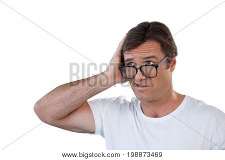 Confused mature man wearing eyeglasses scratching head while looking away against white background