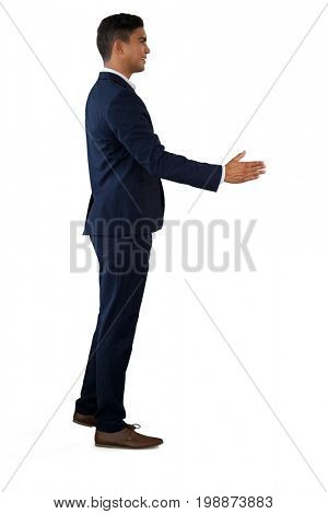 Side view of businessman extending arms for handshake while standing against white background