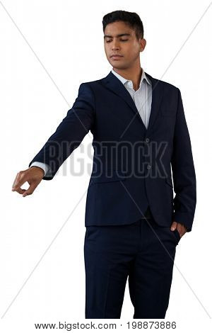 Young businessman with hands in pockets touching invisible interface while standing against white background