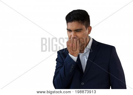 Worried businessman biting nails against white background