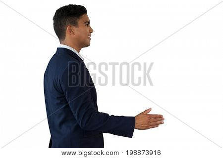Side view of young businessman extending arms for handshake while standing against white background