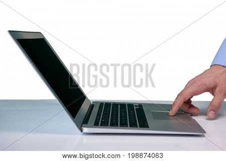 Cropped hand on businessman touching touch pad on laptop against white background