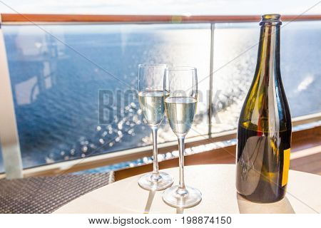 Champagne bottle and flutes glasses on luxury cruise travel for honeymoon holidays. Boat at sea on vacation sunset with celebration drinks.