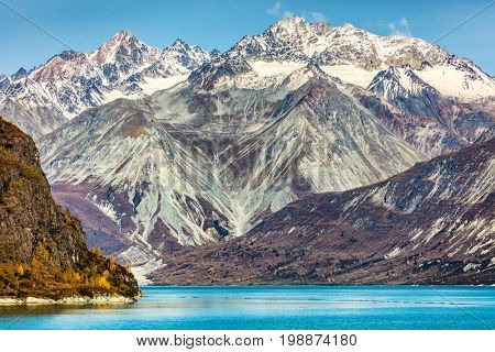 Glacier Bay National Park, Alaska, USA. Alaska cruise travel view of snow capped mountains at sunset. Amazing glacial landscape view from cruise ship vacation showing snowy mountain peaks.