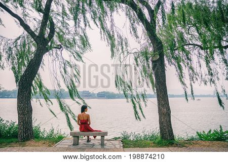 Nature lake woman sitting on park bench relaxing at view of Summer Palace in Beijing, China. Asia travel. Romantic scenery of lady in red dress under weeping willow trees in serenity.