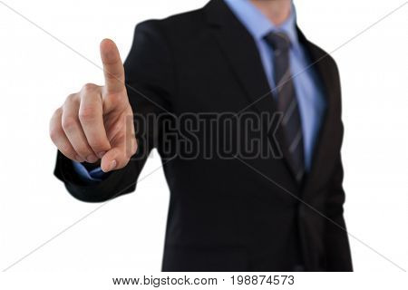 Mid section of businessman touching index finger on invisible screen while standing against white background