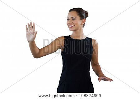Smiling young businesswoman using invisible interface while standing against white background