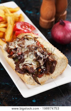 Philly cheese steak sandwich with tomato and french fries