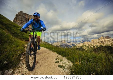 View of cyclist riding mountain bike on single trail in Dolomites, Cinque Torri, South Tirol, Italy