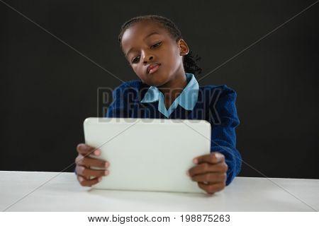 Schoolgirl using digital tablet against black background
