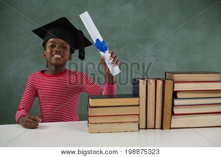 Portrait of schoolgirl in mortar board holding certificate against chalkboard