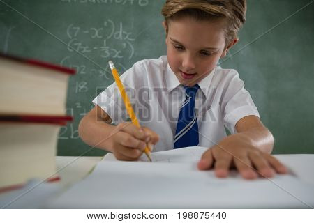Attentive schoolboy doing his homework in classroom
