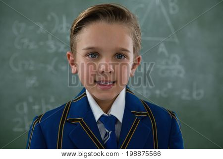 Portrait of smiling schoolboy standing against chalkboard